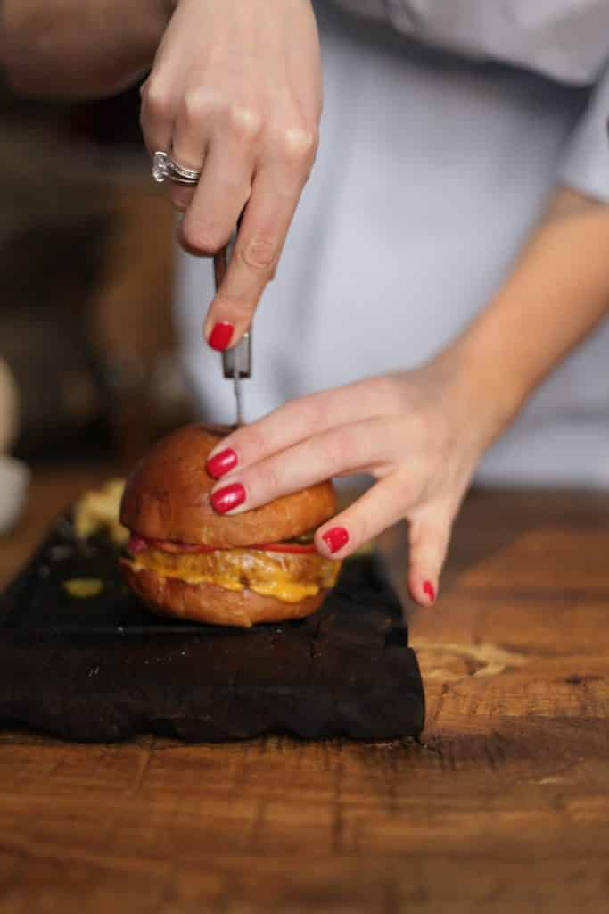 a hand with red painted nails slicing through a hamburger with bun on a wooden cutting board