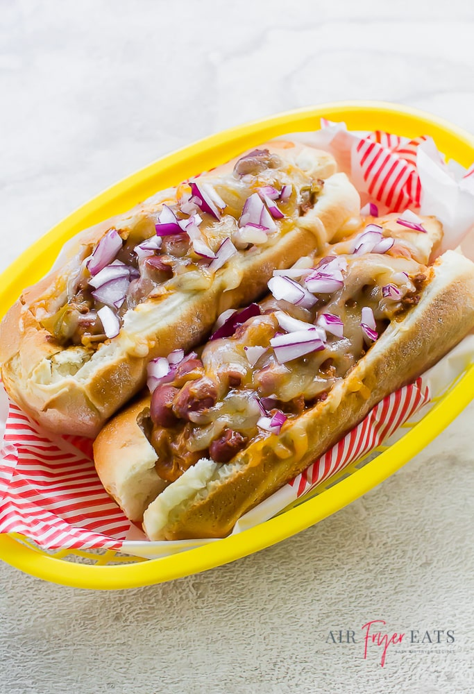 chili cheese dog topped with diced red onion in a yellow basket with red and white paper