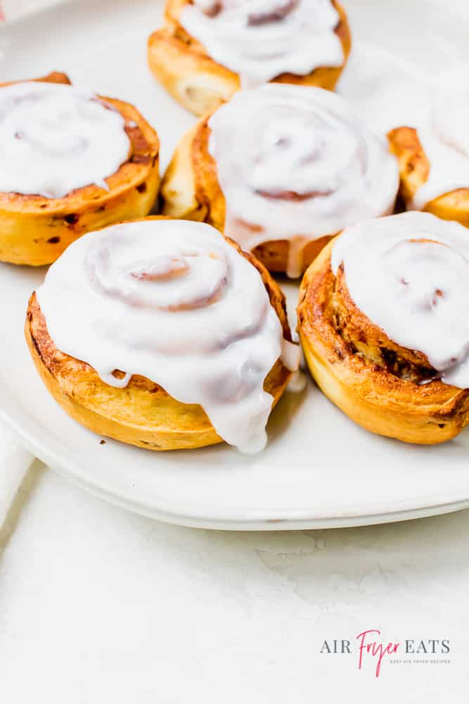 Air Fryer Cinnamon Rolls with white frosting on a white plate