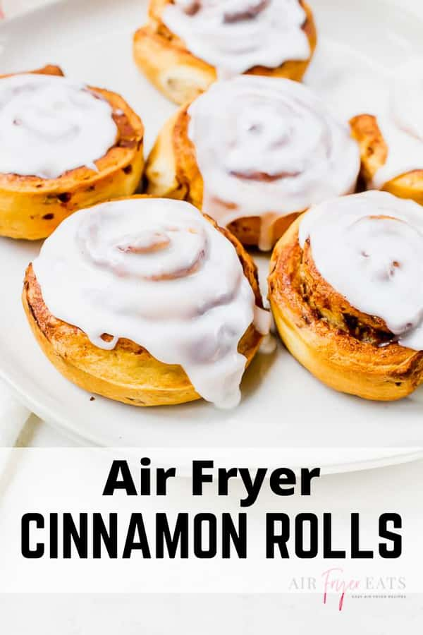 pin showing cooked cinnamon rolls with white frosting on a white plate with words air fryer cinnamon rolls