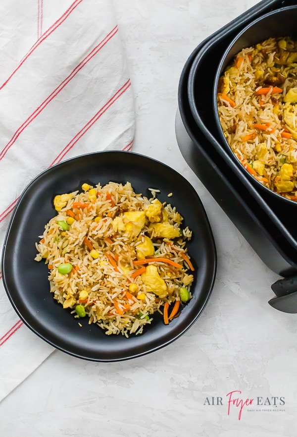 Fried rice on a black plate next to an air fryer basket of fried rice