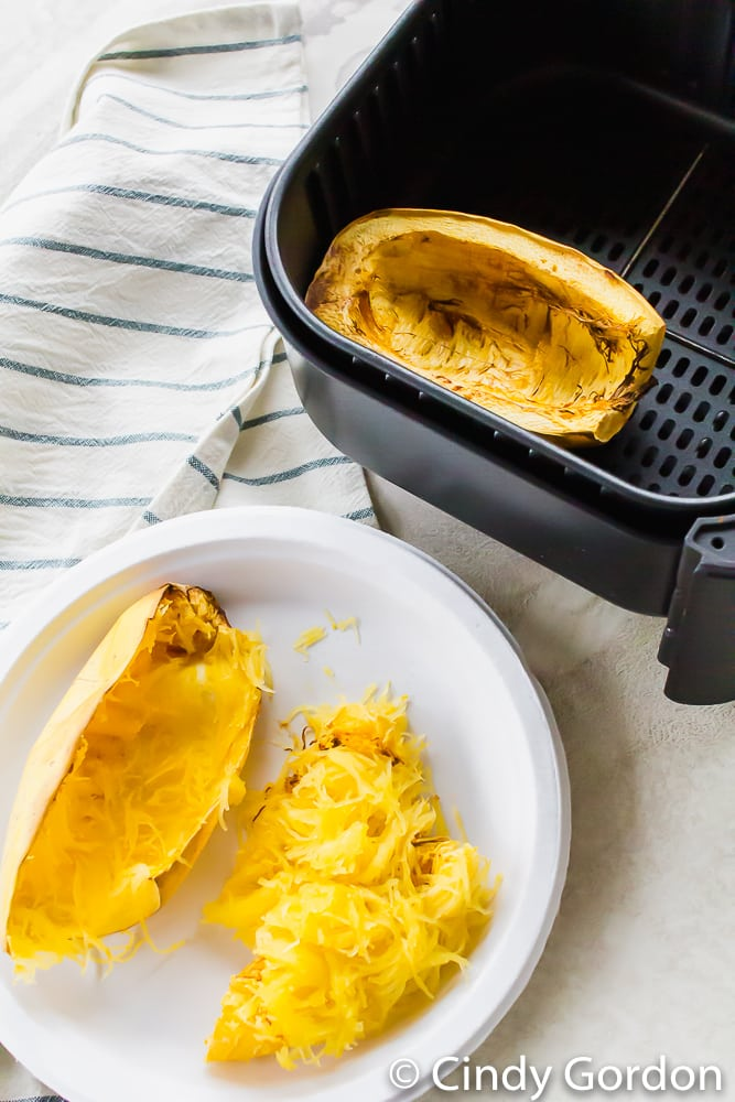 spaghetti squash noodles on a white plate next to an air fryer basket with a squash half inside it