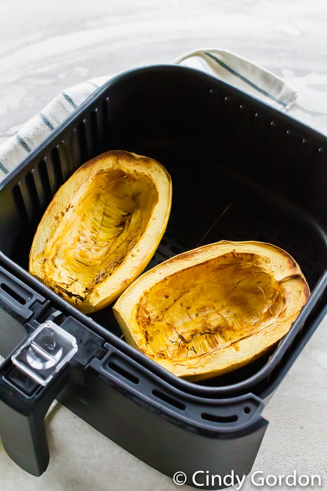 cooked spaghetti squash halves in an air fryer basket