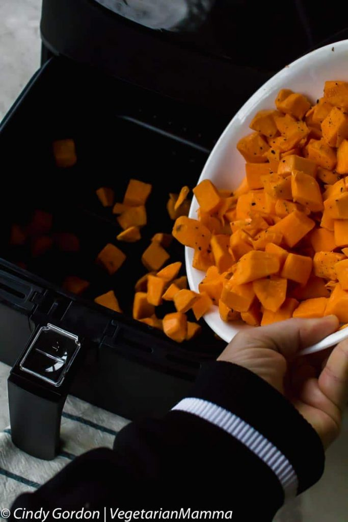 hand dumping cubed sweet potatoes from a white bowl into a black air fryer basket.