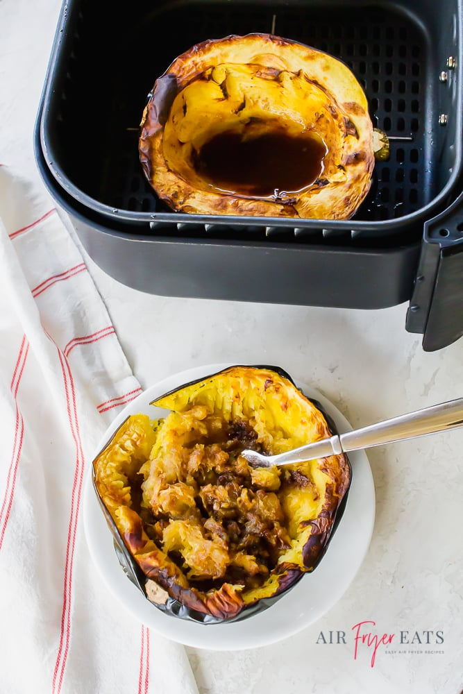 Picture of cooked acorn squash on a white plate and the other half in a black air fryer basket. Both acorn squash halves are cooked and have a brown sugar liquid mixture in the center.