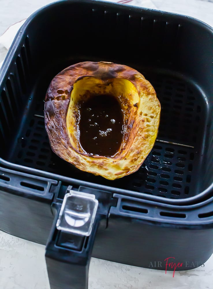 Cooked air fryer acorn squash with puddle of brown sugar liquid mixture in center inside of a black air fryer basket.