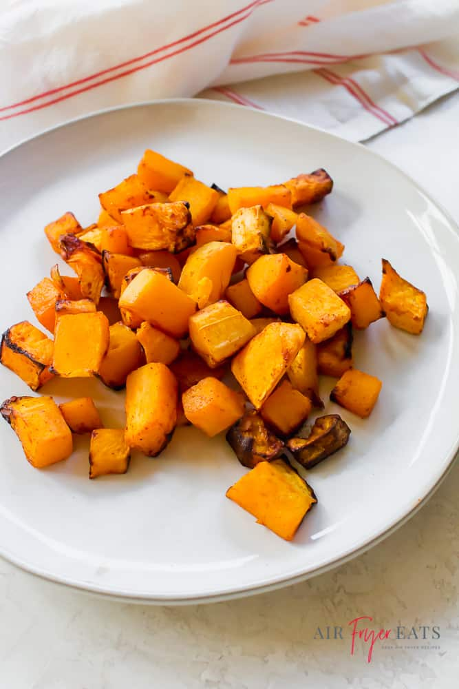 cooked butternut squash on a white plate with a white and red napkin in the background