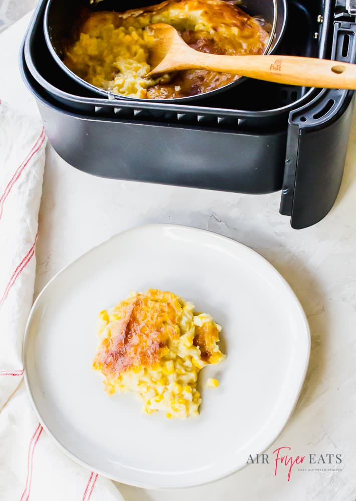 overhead shot of corn pudding on white plate and a bowl of creamed corn casserole in a black air fryer basket with a wooden spoon