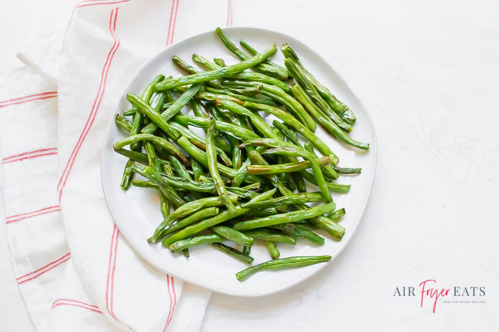 cooked green beans on a white plate next to a red striped kitchen towel on a marble countertop