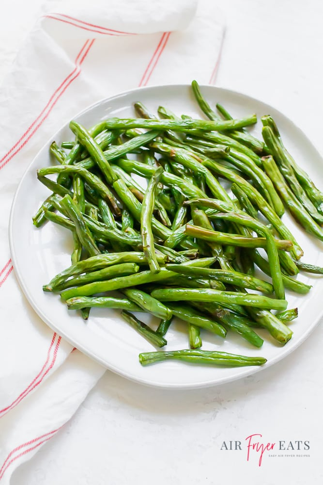 cooked green beans on a white plate next to a red striped kitchen towel