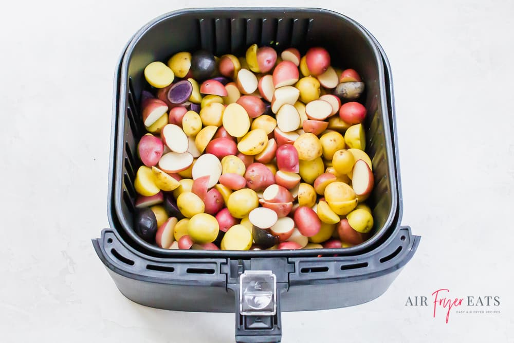 uncooked potatoes in a black air fryer basket