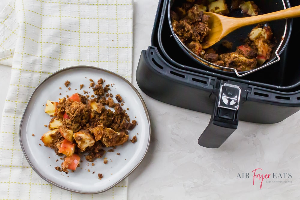 air fryer apple crisp on a white plate and in a black air fryer basket