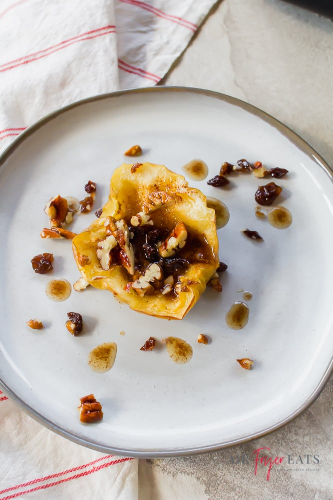 Vertical picture of a white plate with one half of an air fryer spiced apple topped with a pecan raisin mixture.