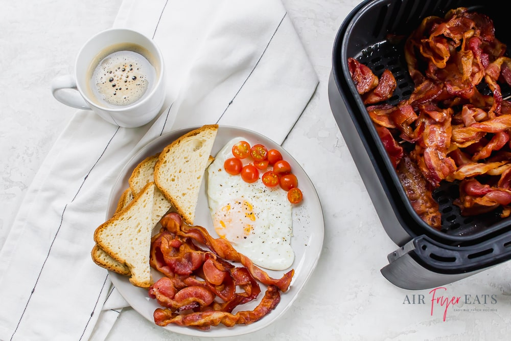 Overhead shot of coffee in a white mug to the left. Center of the photo is a white plate with air fryer bacon, toast cut into triangles, fried egg and cherry tomatoes. On the right is a black air fryer basket full of cooked bacon.