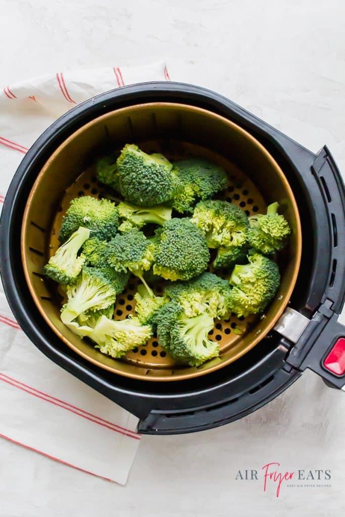 raw green broccoli in a round air fryer basket
