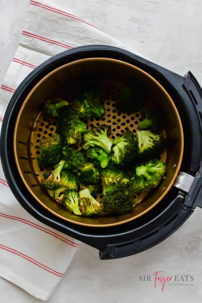 Cooked air fryer broccoli in a black and gold air fryer round basket