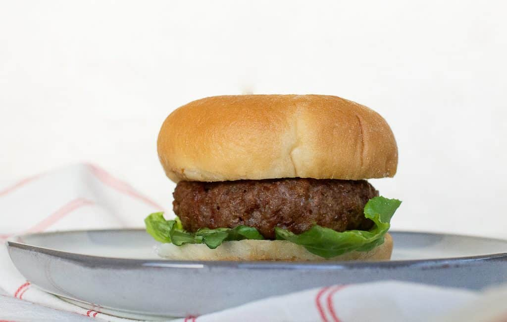 air fryer hamburger with lettuce on a bun on a white plate and white background. This horizontal picture has a white and