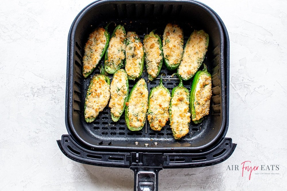 horizontal overhead style photo of cooked jalapeno poppers in a black air fryer basket