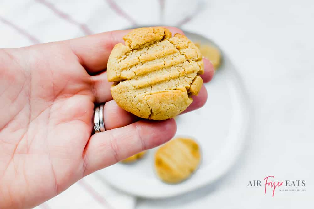 Someone holding a peanut butter cookie over a plate of cookies