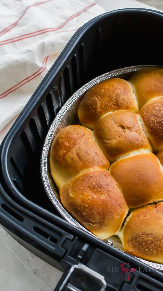 Side angle of frozen rolls cooked in an air fryer. Rolls  are in a foil pan in a black air fryer basket