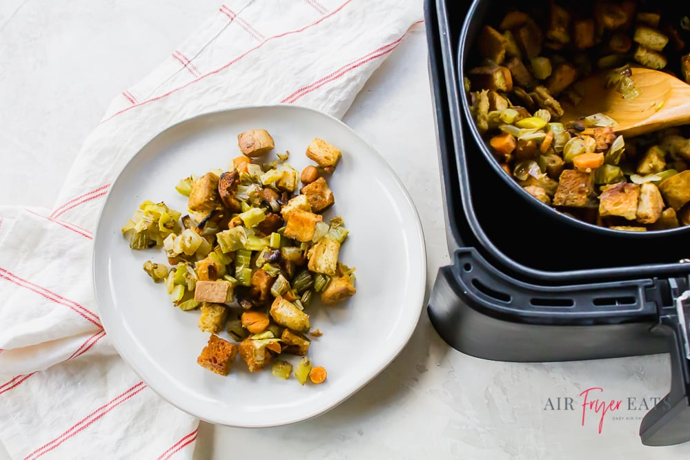 air fryer stuffing on a white plate on a white back ground with a white and red striped napkin to the left. On the right of the horizontal picture is a black air fryer basket with a pot of air fryer dressing with a wooden spoon.