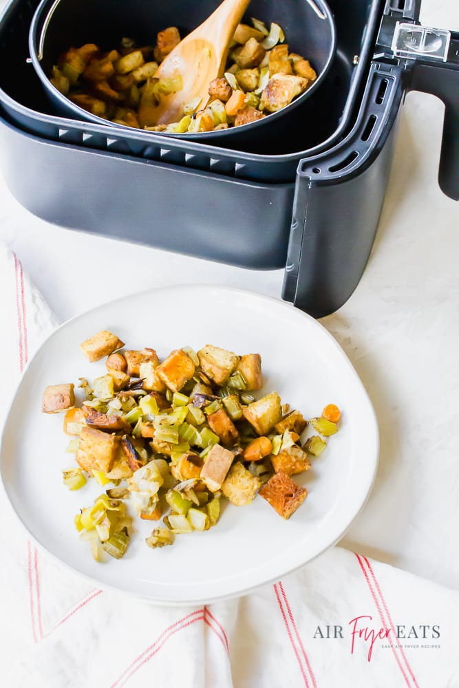 picture of air fryer stuffing in a black air fryer basket with a wooden spoon. air fryer dressing is also on a white plate.