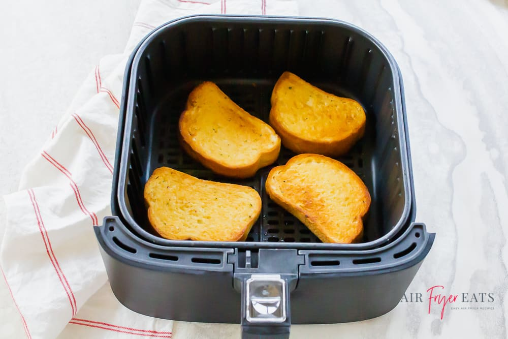 four pieces of texas toast in black air fryer basket