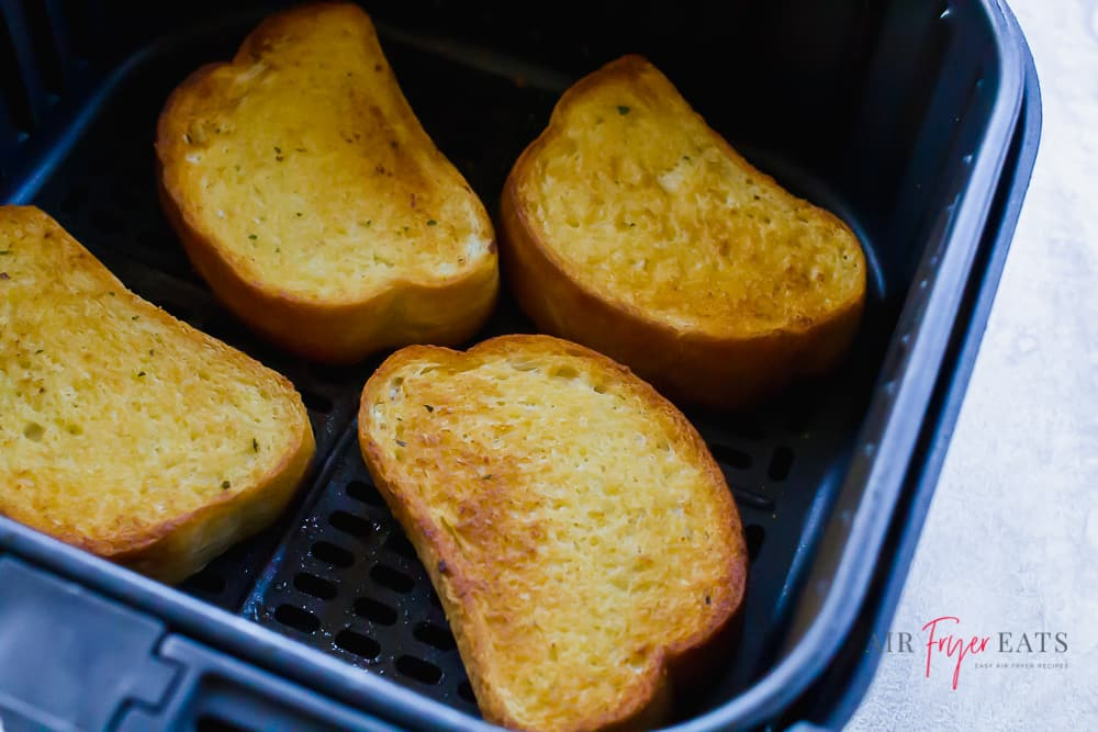 upclose shot of 4 pieces of texas toast in air fryer basket