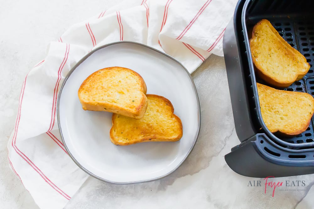 two slices of texas toast on white plate and on the right there is a black air fryer basket with 2 slices of texas toast