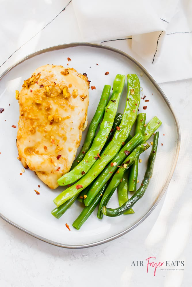 Overhead shot of ginger chicken with green beans on a white plate