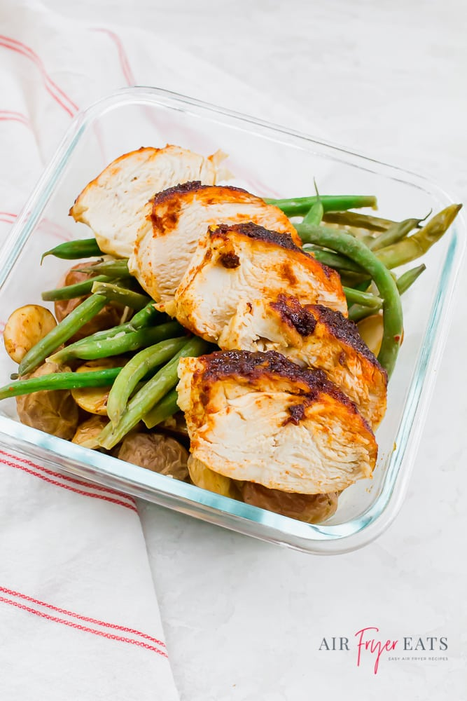 Seasoned chicken, green beans, and roasted potatoes in a meal prep container