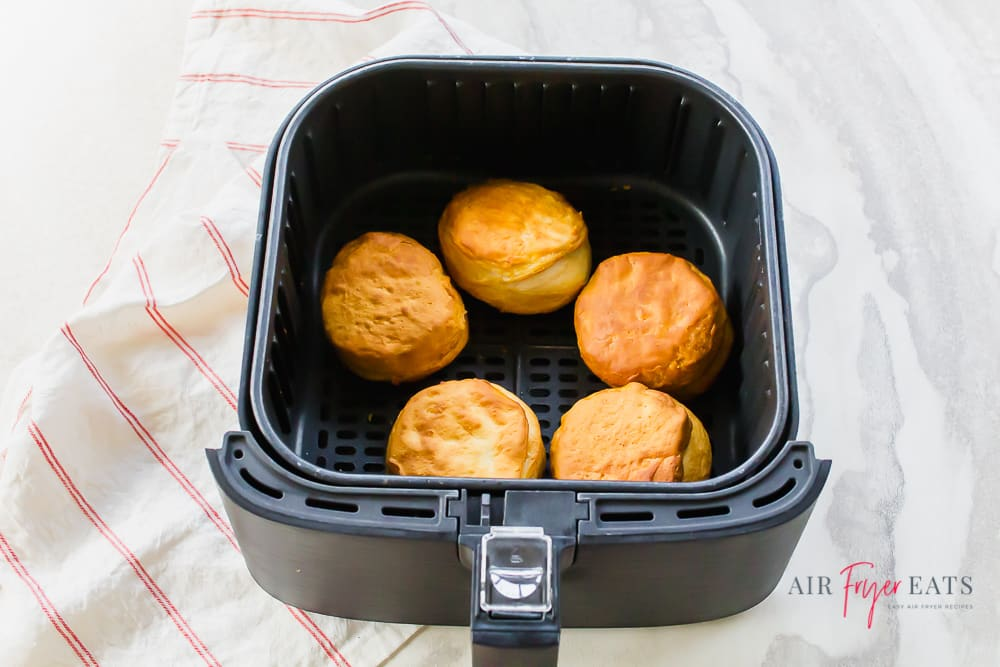 cooked biscuits in a black air fryer basket.