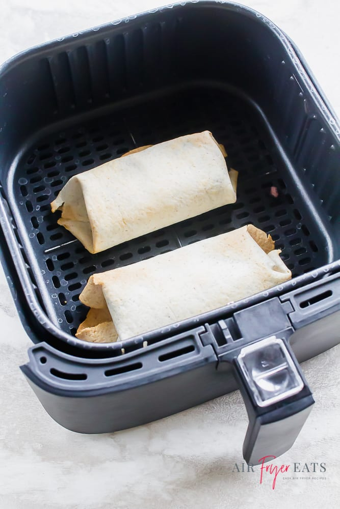 two burritos in the basket of an air fryer, lightly browned.