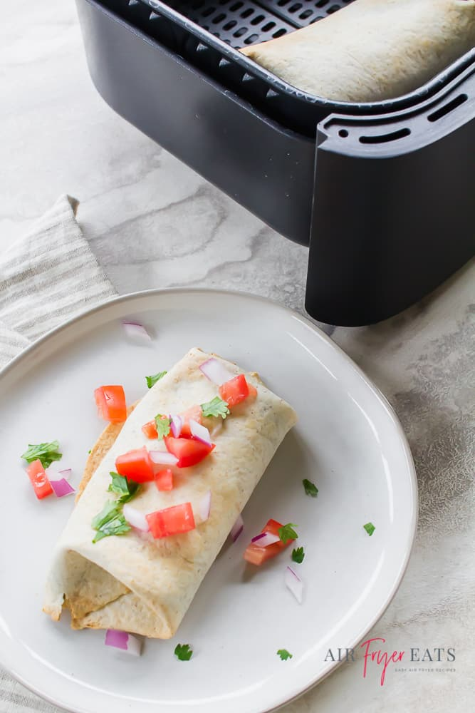 a burrito garnished with diced tomatoes and green herbs on a white plate beside a black air fryer basket