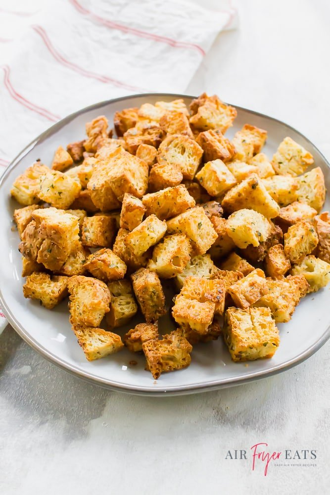 Overhead shot of a white plate covered in homemade croutons