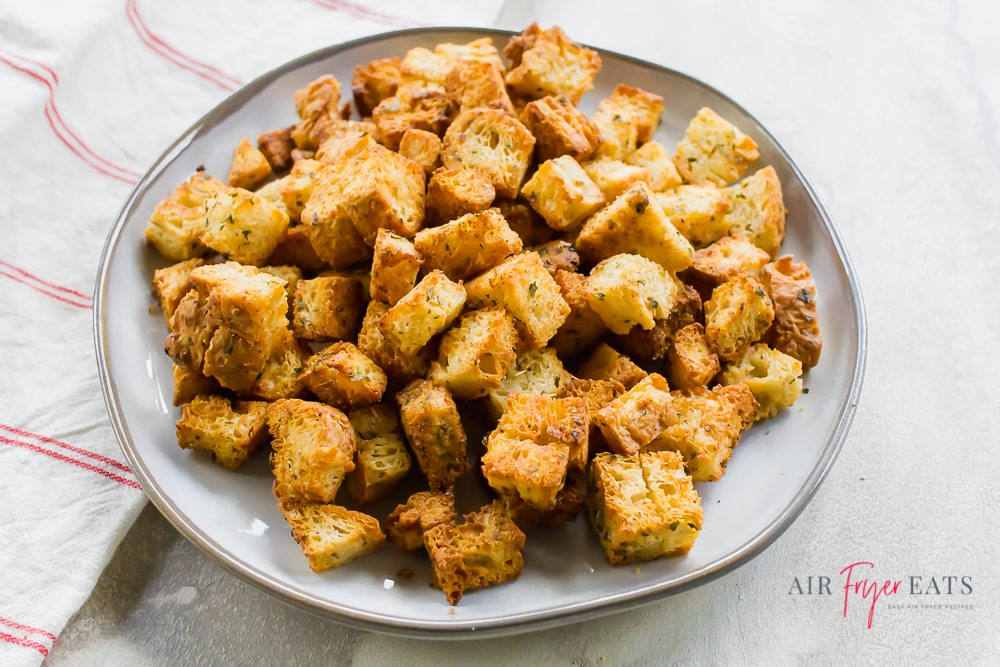 Homemade croutons on a white plate and granite countertop with a striped kitchen towel