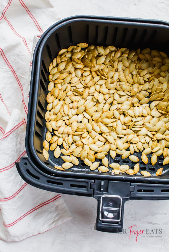 vertical photo of a black air fryer basket with cooked pumpkin seeds