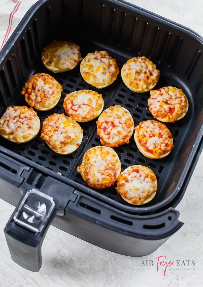 vertical photo of bagel bites in a black air fryer basket