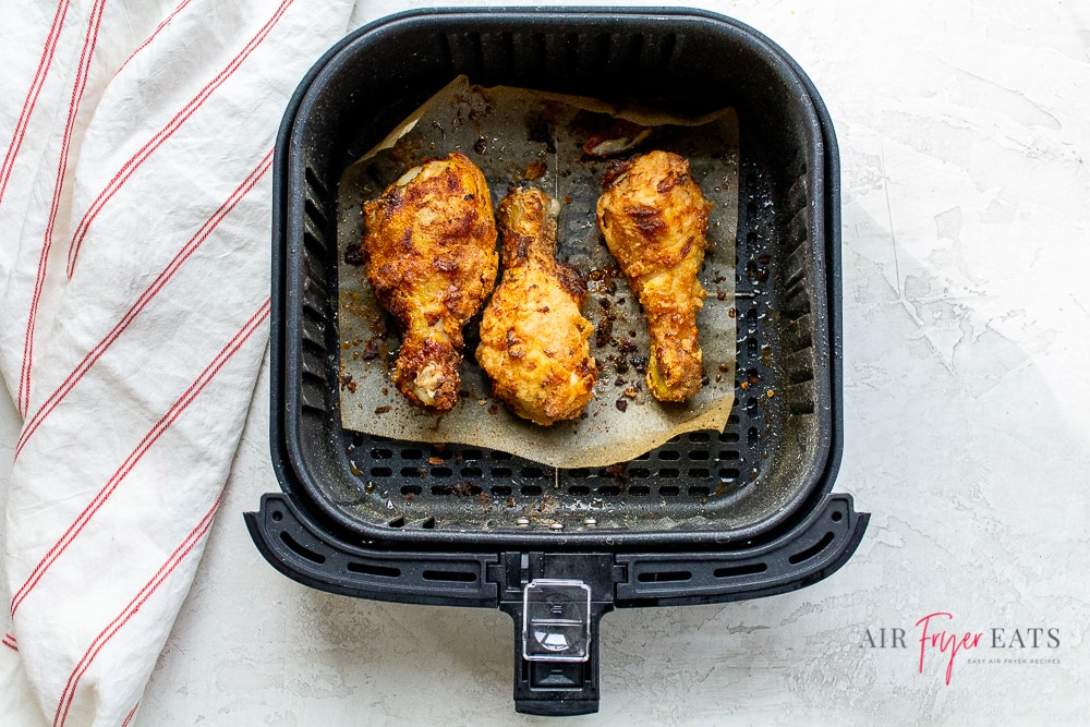 black air fryer basket with cooked crispy brown air fryer chicken inside