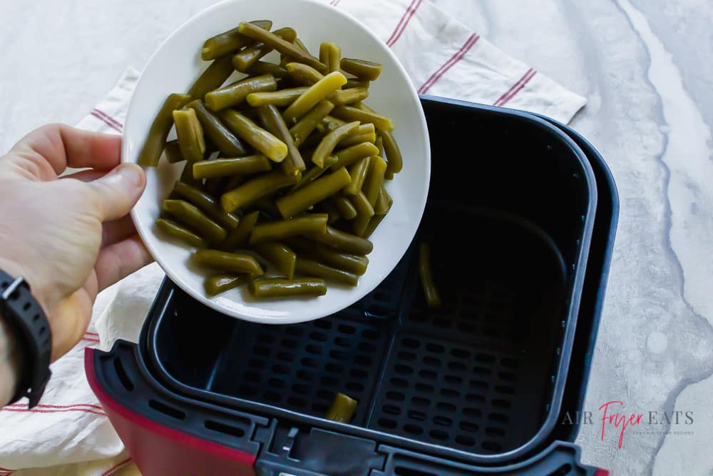 White bowl of green beans being poured into a black and red air fryer basket.