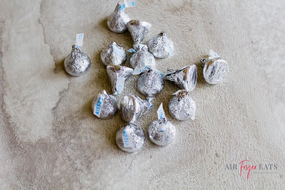 Hershey's kisses wrapped in silver foil in a pile on the counter.