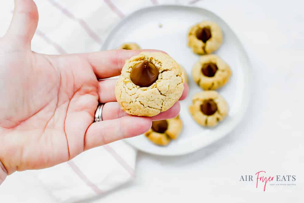 A hand holding a peanut butter blossom cookie above a plate of cookies.