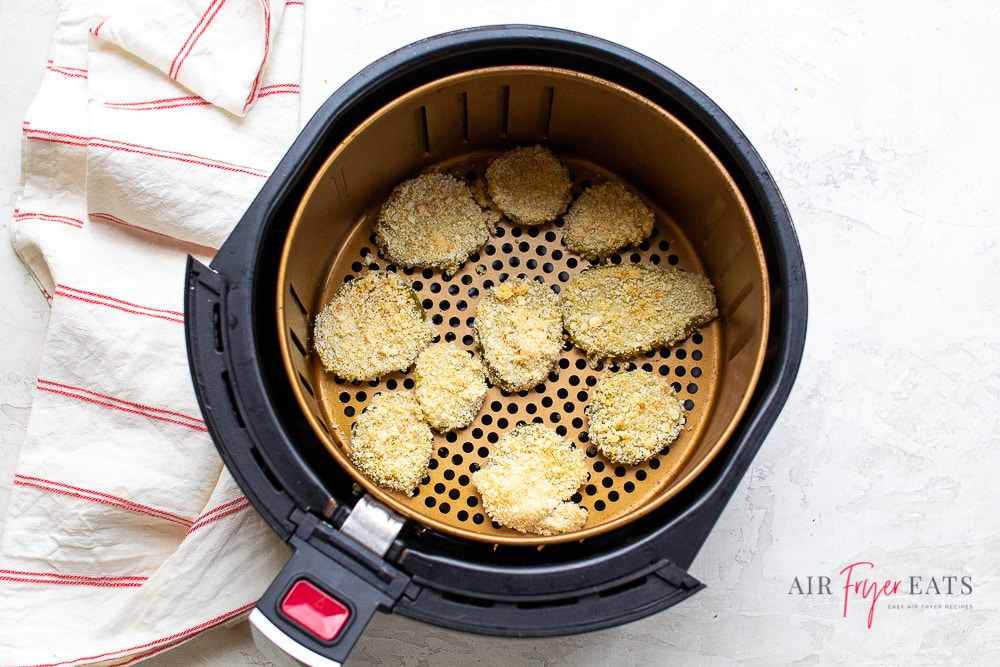 overhead shot of air fryer pickles in a round air fryer basket
