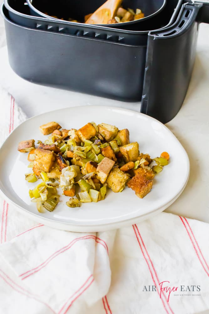 Air Fryer Stuffing on a white plate and also in a black air fryer basket