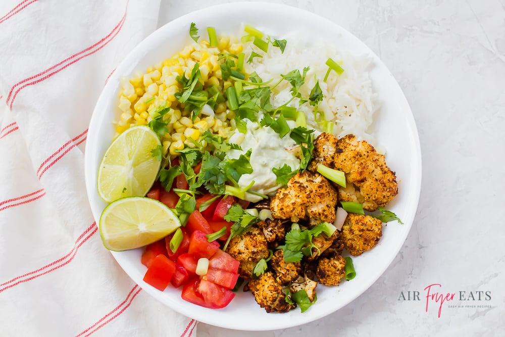 A cauliflower taco bowl with corn, tomatoes, lime crema, white rice, and cilantro