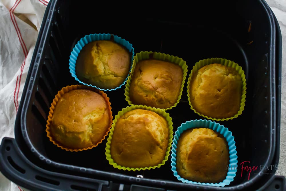 cooked cupakes in a black air fryer basket
