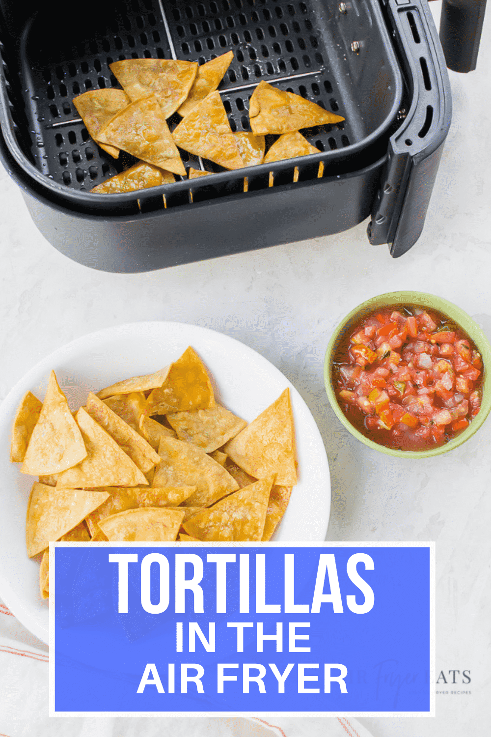 vertical picture. tortilla chips on a white plate at the bottom. red salsa in a green bowl and chips in an air fryer basket.