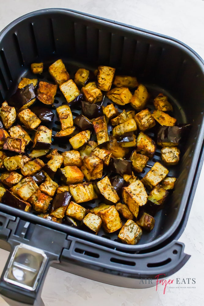 square Air fryer basket filled with roasted eggplant pieces.