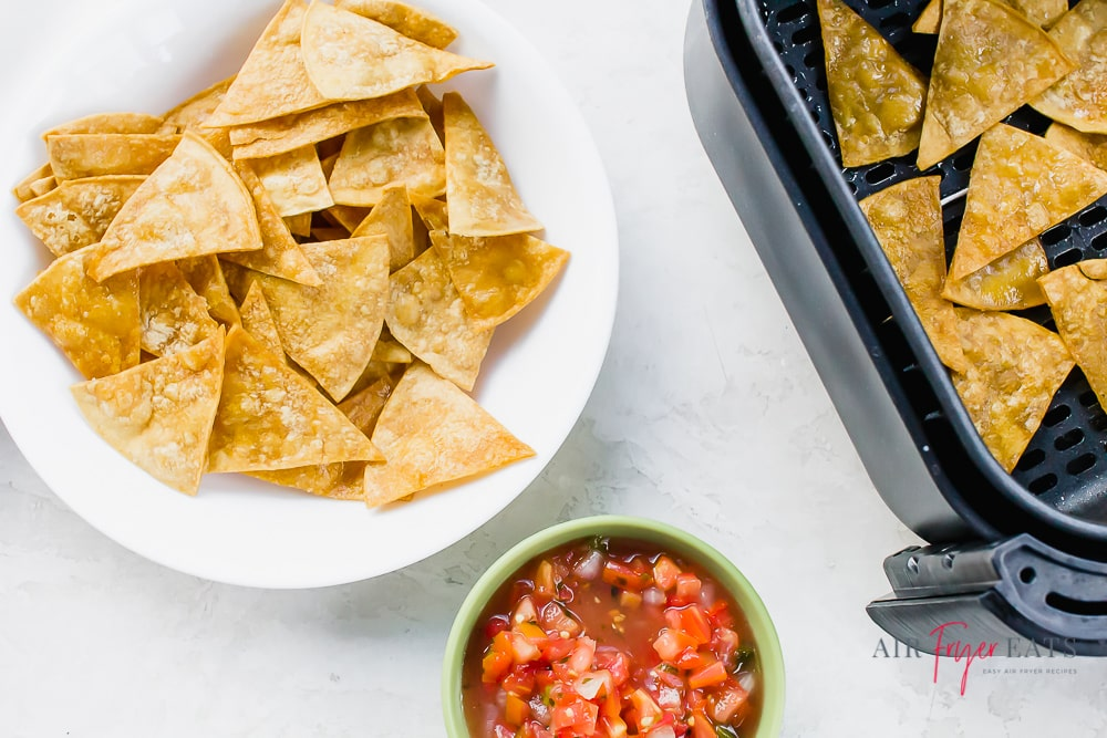 a white plate of chips with a small bowl of tomato salsa and an air fryer basket of tortilla chips
