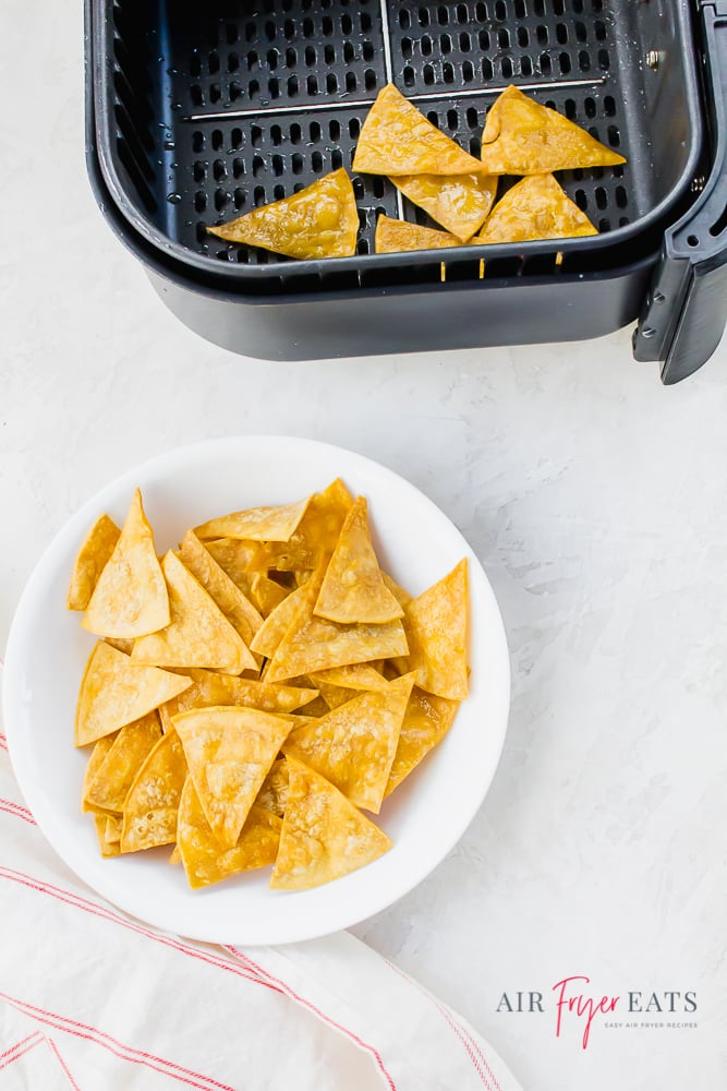 a white plate of tortilla chips next to a air fryer basket of tortilla chips